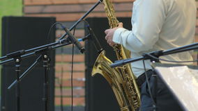 Musicus het spelen saxofoon in het stadium, 4k close-up stock video