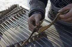 Musicus van de handen de vuile oude die straat op een oud muzikaal instrument wordt gespeeld royalty-vrije stock fotografie
