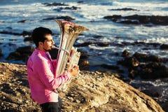 Musicusspel aan Tuba op oceaankust ontspan stock afbeeldingen