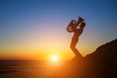 Musicusspel Tuba Silhouette op de overzeese kust bij zonsondergang RomanÑ  e Royalty-vrije Stock Afbeelding