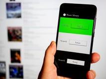 Musik app i telefon med datorskärmen Begrepp arkivfoto