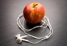 Musik, die Apfel spielt, in dem Kopfhörer angeschlossen werden lizenzfreie stockbilder