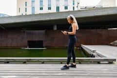 Musik för kvinnalöparestart på smartphonen, innan att köra arkivbild