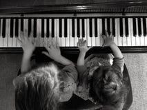Musik för lek för två barn på piano Arkivbild
