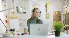 Musik för Yung glad kvinnalisteningto vid bärbara datorn stock video