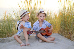 Musik för barnlek tillsammans på stranden Arkivfoto