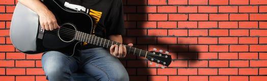 Musik - fragmentmanlek en svart akustisk gitarr Arkivfoto