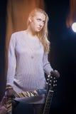 Musik-Konzept und Ideen Junge blonde weibliche Aufstellung mit Gitarre Stockfotografie