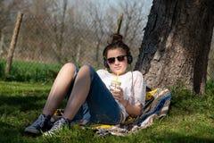 Musik och dricksvatten för tonåringflicka parkerar lyssnande i royaltyfri bild
