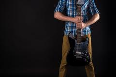 Musik och konst Gitarristen rymmer den elektriska gitarren med hans händer, på en svart isolerad bakgrund leka för gitarr horison royaltyfri foto