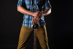Musik och konst Gitarristen rymmer den elektriska gitarren med hans händer, på en svart isolerad bakgrund leka för gitarr horison Arkivbild