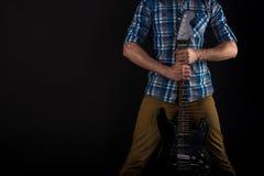 Musik och konst Gitarristen rymmer den elektriska gitarren med hans händer, på en svart isolerad bakgrund leka för gitarr horison Royaltyfri Fotografi