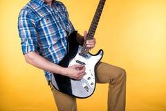 Musik och konst Gitarristen spelar den elektriska gitarren på en gul bakgrund leka för gitarr Horisontal inrama Fotografering för Bildbyråer