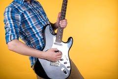 Musik och konst Gitarristen spelar den elektriska gitarren på en guling isolerad bakgrund leka för gitarr Horisontal inrama Arkivfoton