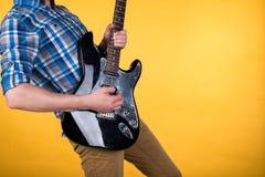 Musik och konst Gitarristen spelar den elektriska gitarren på en guling isolerad bakgrund leka för gitarr Horisontal inrama Arkivfoto