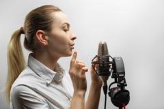 Musik, showbusiness, folk och stämmabegrepp - sångare med hörlurar och mikrofonen som sjunger en sång i inspelningstudio, arkivfoton