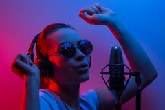 Musik, showbusiness, folk och stämman av en sångare eller discjockeyn med hörlurar med exponeringsglas och en mikrofon som sjunge arkivbild