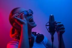 Musik, showbusiness, folk och stämman av en sångare eller discjockeyn med hörlurar med exponeringsglas och en mikrofon som sjunge royaltyfri fotografi