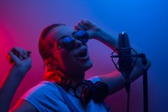 Musik, showbusiness, folk och stämman av en sångare eller discjockeyn med hörlurar med exponeringsglas och en mikrofon som sjunge royaltyfria foton