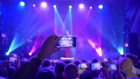 Musikalische Kunst, Handys in den Händen des Bewunderers schießen Video des Rockkonzerts auf beleuchtetem Stadium stock video