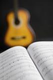 Musikalische Spannweiten und Gitarre auf Hintergrund Stockfotografie