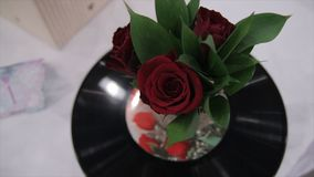 Musikalischer Blumenstrauß von Rosen und von Aufzeichnung Schöner Blumenstrauß r von roten Rosen ist auf Grammvinyl Rosen und Auf Stockfoto