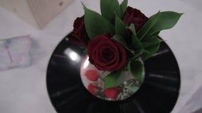 Musikalisk bukett av rosor och rekordet Härlig bukett r av röda rosor är på gramvinyl Rosor och rekord Tappning lager videofilmer