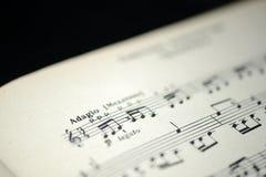 Musikalisk ` för tempo` Adagio i en gammal musikanteckningsbok royaltyfria bilder