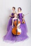 Musikalisk trio i aftonkappor Arkivfoton