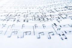 Musikaliska anmärkningar på det krabba vita arket av papper Selektivt fokusera arkivbilder
