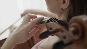 Musikaliskt hantverk av positiv kvinnlig violoncellist på kameran i ljust rum lager videofilmer