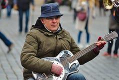 Musikant, das Gitarre am alten Marktplatz spielt stockfotografie