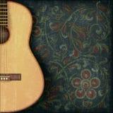 Musikbakgrund med gitarren och den blom- prydnaden Arkivfoto