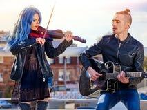 Musikband för festivalmusik Vänner som spelar på gitarren och fiolen i stad, parkerar Royaltyfria Foton