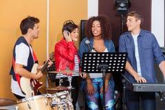 Musikband som tillsammans utför i inspelningstudio royaltyfria foton