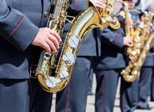 Musikbandmusiker för militär mässing med guld- saxofoner Fotografering för Bildbyråer