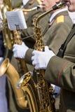 Musikbandmusiker för militär mässing spelar saxofoner ståtar på Arkivfoto