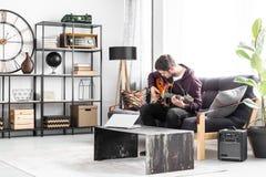 Musiker auf schwarzer Couch lizenzfreie stockfotografie