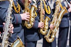 Musiker av arméorkesteren spelar hans guld- saxofoner Arkivfoto