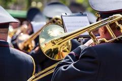 Musiker av den militära orkesteren som spelar på den guld- trombonen royaltyfri foto