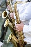 Musiker av den militära orkesteren spelar saxofoner Arkivfoto