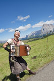 Musiker, der das Akkordeon, jodelnd in den Alpen spielt Lizenzfreie Stockfotografie