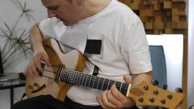 Musiker, der die Handgelenkschmerz beim Spielen der E-Gitarre im Hauptmusikstudio hat stock video