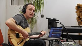 Musiker, der E-Gitarre im Hauptmusikstudio singt und spielt stock footage