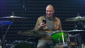Musiker, der Handy verwendet und Becken schlägt stock video footage