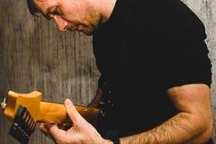 Musiker en man i svart som spelar en svart elektrisk gitarr arkivbild