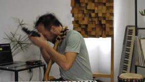 Musiker i den hem- musikstudion som p? s?tter h?rlurar och att testa lager videofilmer
