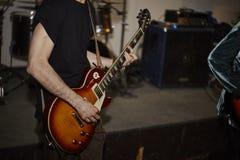 Musiker i svarta t-skjorta lekar på den elektriska gitarren royaltyfria bilder