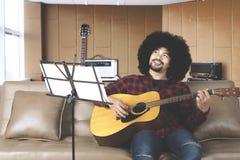 Musiker med afro hår som spelar gitarren i en inspelningstudio arkivfoton