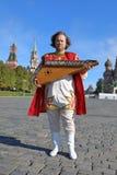 Musiker med anseende för gusli för musikinstrument på röd fyrkant Royaltyfri Fotografi